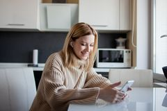 Beautiful young woman in a cozy sweater sitting in the kitchen uses subscription services and media applications. A girl at home with a phone in her hands and royalty free stock images