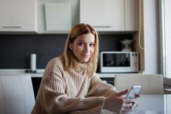 Beautiful young woman in a cozy sweater sitting in the kitchen uses subscription services and media applications. A girl at home with a phone in her hands and stock photos