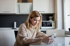 Beautiful young woman in a cozy sweater sitting in the kitchen uses subscription services and media applications. A girl at home with a phone in her hands and stock photography