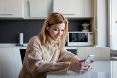 Beautiful young woman in a cozy sweater sitting in the kitchen uses subscription services and media applications. A girl at home with a phone in her hands and royalty free stock photo