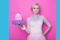 Beautiful young woman with cream colored dress holding pink and purple gift boxes Royalty Free Stock Photo