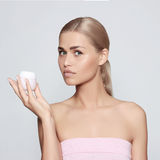 Beautiful young woman. With cream in the hands of Stock Photo