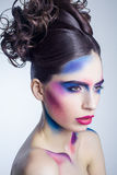 Beautiful young woman with creative colored makeup and curly collected hairstyle and painted colored body. Stock Image