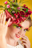 Beautiful young woman with creative flower cap. Artistic makeup with long feather artificial eyelashes and bright colourful eyeshadow Royalty Free Stock Images