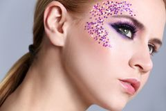 Beautiful young woman with creative makeup. On color background, closeup Stock Image