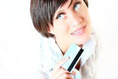 Beautiful young woman with credit card. Thinking what to buy Stock Photography