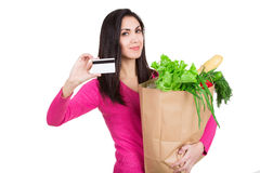 Beautiful young woman with credit card holding paper bag with gr Stock Photos