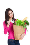 Beautiful young woman with credit card holding paper bag with gr Royalty Free Stock Photos