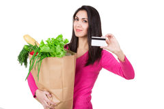 Beautiful young woman with credit card holding paper bag with groceries. Isolated. Shopping and groceries concept. Beautiful young woman with credit card Stock Image