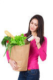 Beautiful young woman with credit card holding paper bag with groceries. Isolated. Shopping and groceries concept. Beautiful young woman with credit card Stock Photos