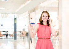 Beautiful young woman with credit card  In shopping mall Stock Images