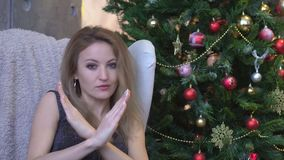 Beautiful young woman with crossed hands showing stop gesture over christmas tree background stock video