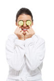 Beautiful young woman with cucumber on eyes. Royalty Free Stock Photos