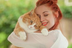 Beautiful young woman cuddling with cute red cat Stock Images