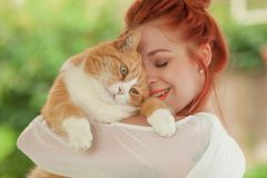 Beautiful young woman cuddling with cute red cat Royalty Free Stock Photo