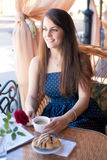 Beautiful young woman with cup of at a cafe Royalty Free Stock Image