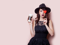 Beautiful young woman with cup of coffee and heart shaped toy on Royalty Free Stock Photos