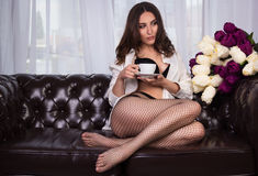 Beautiful young woman with a cup of coffee. Sexy woman in white man`s shirt and stockings on sofa. Pensive girl with a cup of tea. Royalty Free Stock Photography