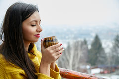 Beautiful young woman with cup of coffee on winter background. On the balcony Royalty Free Stock Photography