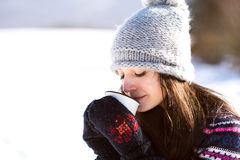 Beautiful young woman with cup of coffee in winter nature Royalty Free Stock Photo