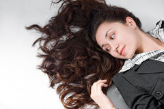 Beautiful young woman with curly brown hair laying Royalty Free Stock Photography