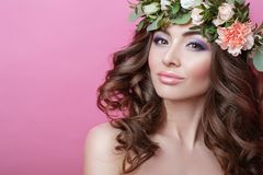 Beautiful young woman with curly hair and flower wreath on her head on pink background Beauty girl with flowers hairstyle Perfect royalty free stock photography