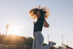 Beautiful young woman with curly hair happily jumping royalty free stock image