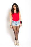 Beautiful young woman curly hair, jeans shorts and red tank top. Beautiful and young girl pin up with a red tank top and jeans shorts and fishnet stockings. On Stock Image