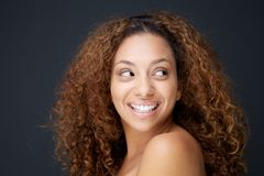 Beautiful young woman with curly hair laughing and looking away Royalty Free Stock Photos