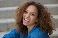 Beautiful young woman with curly hair smiling outdoors Royalty Free Stock Image