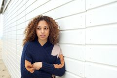Beautiful young woman with curly hair and sweater posing outdoors Stock Photography