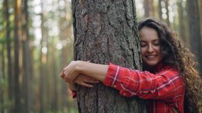 Beautiful young woman with curly hair wearing bright shirt is hugging tree enjoying nature and smiling with closed eyes