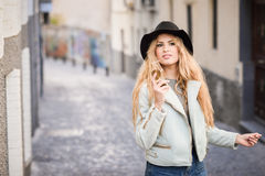 Beautiful young woman with curly hair wearing hat Stock Images