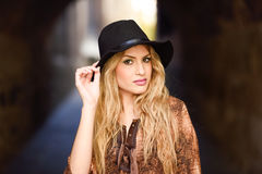 Beautiful young woman with curly hair wearing hat Stock Photo