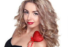 Beautiful young woman with curly long hair holding heart Royalty Free Stock Photo