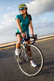 Beautiful young woman cycling on the road. Stock Photos