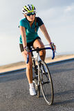 Beautiful young woman cycling on the road. Royalty Free Stock Photo
