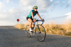 Beautiful young woman cycling on the road. Stock Photo