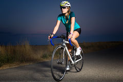 Beautiful young woman cycling on the road. Royalty Free Stock Photography