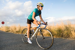 Beautiful young woman cycling on the road. Portrait of beautiful young woman cycling on the road Royalty Free Stock Images