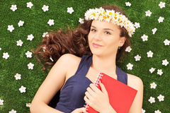 Beautiful young woman with a daisy hair wreath lying on a grass. Beautiful young woman with a daisy hair wreath lying on a green grass with daisy flowers Stock Photos
