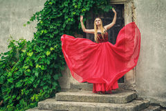 Beautiful young woman dancing in fashion red dress Stock Photos