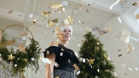 Beautiful young woman is dancing among golden confetti. Blonde girl dancing among confetti on the celebrating party. Happy New Year. Merry Christmas. Slow stock footage