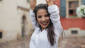 Beautiful young woman dancing and having fun with umbrella on the street of the old city after rain. stock video footage