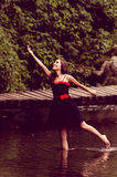 Beautiful young woman dancing in a lake forest Stock Photo