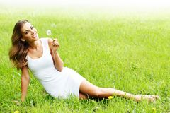 Beautiful young woman with dandelion Royalty Free Stock Images