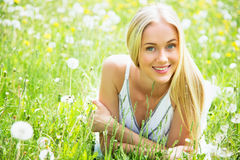 Beautiful young woman among dandelions Stock Photography