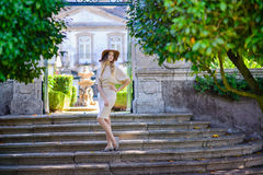 Beautiful young woman with dark hair in elegant beige dress posing on the stairs stock photo