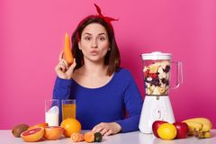 Beautiful young woman with dark hair, keeps lips rounded, holds carrot in hands, makes fresh smoothies, has blender filled with royalty free stock photography