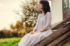 Beautiful young woman with dark hair sitting on the steps near t Royalty Free Stock Images
